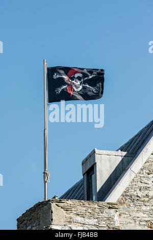 Jolly Roger pirate flag flies over Baltimore Castle in West Cork in Ireland - Stock Photo