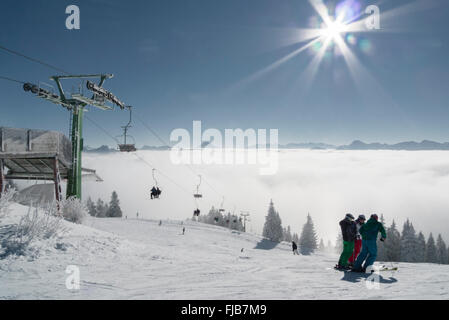 Skiers standing next to a chair lift in front of the alpine panorama at Brauneck ski resort in bright sunlight,Bavaria,Germany - Stock Photo