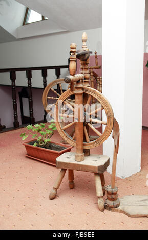 Nice ancient wooden spinning wheel in home interior - Stock Photo