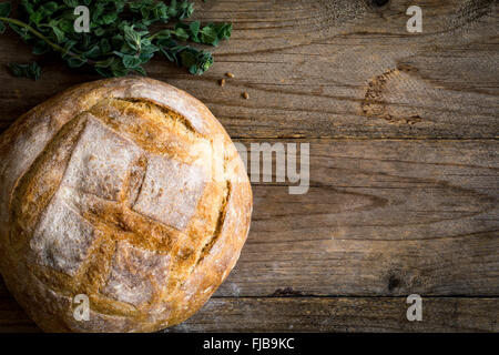 Round loaf of bread, freshly baked sourdough bread on wooden background. Chalk board and bunch of fresh oregano - Stock Photo