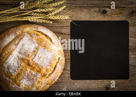 Chalkboard, loaf of bread and wheat ears on wooden background, overhead view - Stock Photo