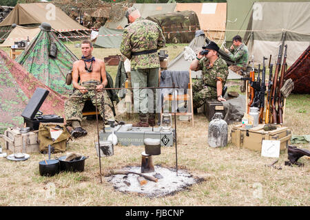 War and Peace Show, England. Second world war re-enactment. German soldiers sitting relaxing with food cooking over - Stock Photo
