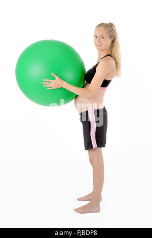 Pregnant woman holding balance yoga ball against belly. - Stock Photo