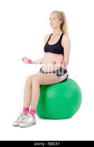 Pregnant woman on yoga balance ball performing bicep curl exercise with weights. - Stock Photo