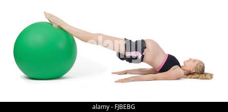 Pregnant woman using yoga ball performing hip raise exercise. - Stock Photo