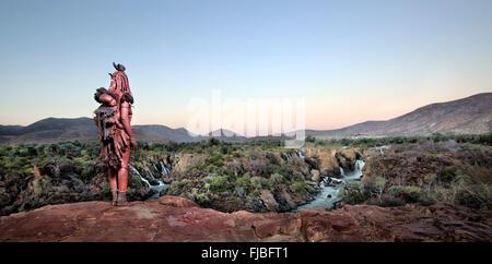 Himba woman overlooking Epupa Falls. - Stock Photo