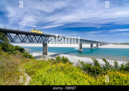Yellow car driving over Haast River Bridge, longest single lane bridge in New Zealand, West Coast, South Island, - Stock Photo