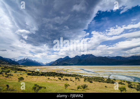 Grassland in front of the wide riverbed of the Tasman River, dramatic clouds, Mount Cook National Park, Pukaki - Stock Photo