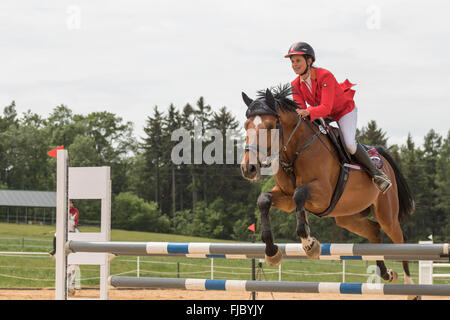 Closeup side view of  horsewoman in red jacket that is jumping - Stock Photo