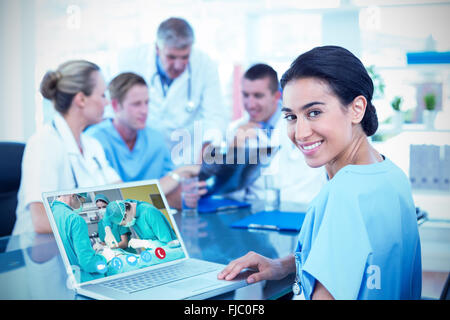 Composite image of beautiful smiling doctor typing on keyboard with her team behind - Stock Photo