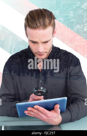 Composite image of businessman looking at digital tablet with magnifying glass - Stock Photo