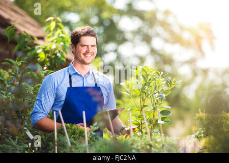 Gardener holding clipboard, in his garden, green sunny nature - Stock Photo