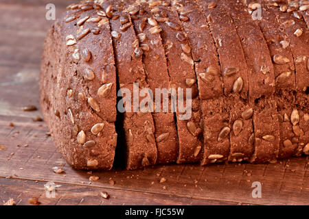 closeup of a sliced loaf of rye bread topped with sunflower seeds on a rustic wooden surface - Stock Photo