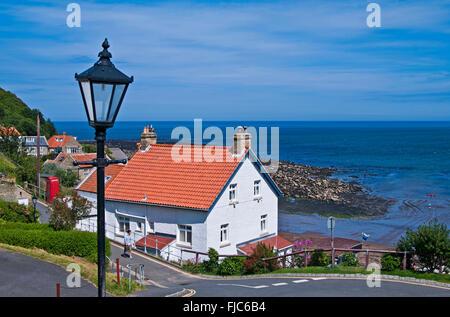 Entrance to the holiday coastal village of Runswick Bay, North Yorkshire, with old fashioned lamp post in foreground, - Stock Photo