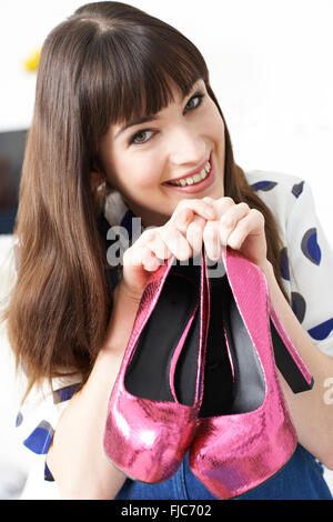 Excited Woman Holding Pair Of New Shoes - Stock Photo