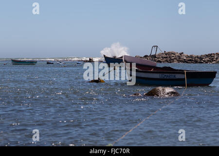 A small fishing boat moored securely in the sheltered harbour of Jacobsbaai while waves break on the rocks - Stock Photo