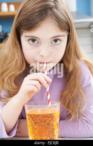 Young Girl Drinking Glass Of Soda Through Straw - Stock Photo