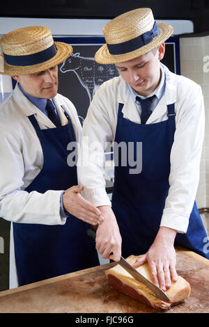 Butcher Teaching Apprentice How To Prepare Sirloin Steak - Stock Photo