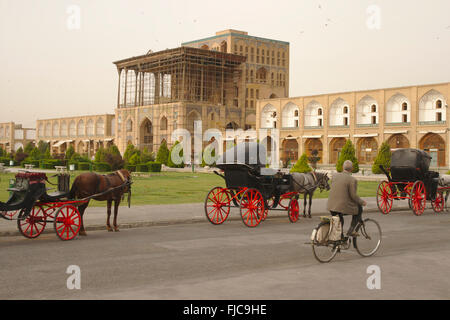 Chariots in front of Ali Qapu Palace on Imam Square (Shah Square), Isfahan, Iran - Stock Photo