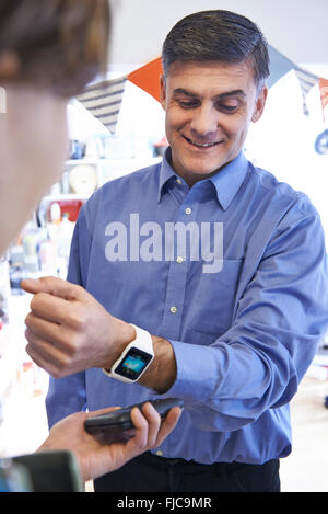 Man Using Contactless Payment App On Smart Watch In Store - Stock Photo