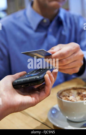 Customer Using Contactless Payment In Coffee Shop - Stock Photo