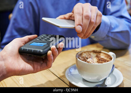 Man Using Contactless Payment App On Mobile Phone In Cafe - Stock Photo