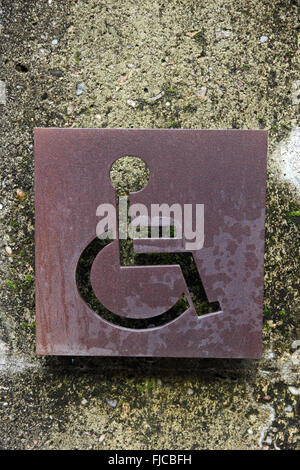 Disabled toilet sign cut into rusted metal sheet - Stock Photo