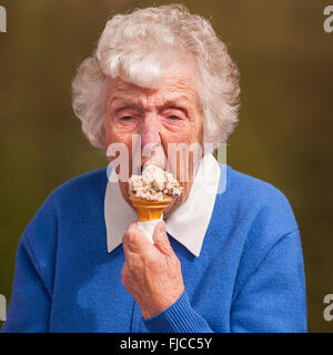 An elderly lady eating an ice cream in the Uk - Stock Photo
