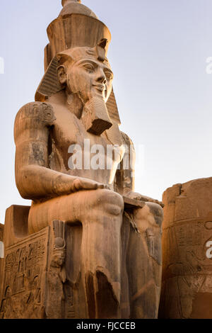 Statue of Ramessess II sitting in front of one of the gates of the Luxor temple.