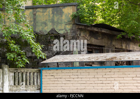 overgrown with moss old building behind the fence - Stock Photo