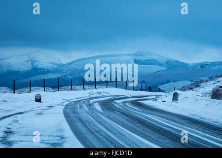 Treacherous driving conditions on an icy road by Stanage Edge in the Peak District. Winter in Derbyshire, England, - Stock Photo