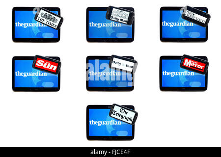 The Guardian newspaper logo on tablet screens surrounded by smartphones displaying the logos of rival newspapers. - Stock Photo