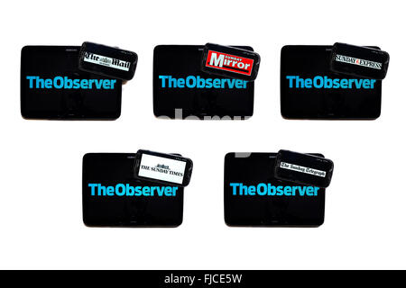 The Observer newspaper logo on tablet screens surrounded by smartphones displaying the logos of rival newspapers. - Stock Photo
