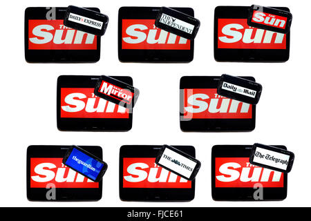The Sun newspaper logo on tablet screens surrounded by smartphones displaying the logos of rival newspapers. - Stock Photo