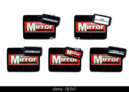The Sunday Mirror newspaper logo on tablet screens surrounded by smartphones displaying the logos of rival Sunday - Stock Photo