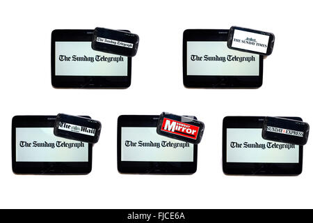 The Sunday Telegraph newspaper logo on tablet screens surrounded by smartphones displaying the logos of rival newspapers. - Stock Photo
