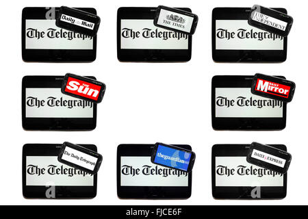 The Telegraph newspaper logo on tablet screens surrounded by smartphones displaying the logos of rival newspapers. - Stock Photo