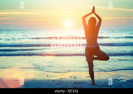 Silhouette of woman practicing yoga on the beach at sunset. - Stock Photo