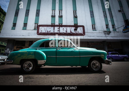 Havana, Cuba. A vintage car rides along Av.da Galiano, just in front of one of the art déco buildings with original - Stock Photo