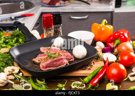 Still Life of Rare Seasoned Roast Beef Slices Sizzling in Hot Frying Pan with Mushrooms and Surrounded by Fresh - Stock Photo