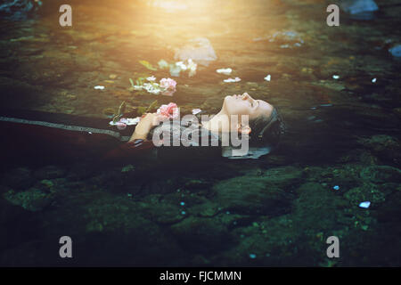 Floating dead woman in dark river . Ophelia conceptual - Stock Photo