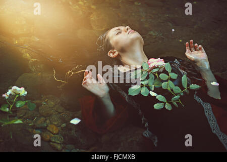Woman in dark water stream and soft sunlight . Romantic and tragedy - Stock Photo