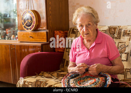 An elderly woman sitting in her room and knitting rug. - Stock Photo