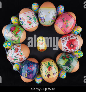 Easter eggs with beautiful ornaments and foil-wrapped chocolate eggs with chicken on a black plate - Stock Photo