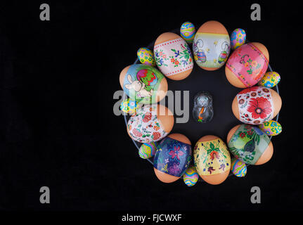 Easter eggs with beautiful ornaments and foil-wrapped chocolate eggs with easter bunny on a black plate - Stock Photo