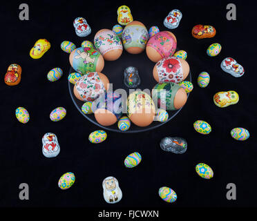 Easter eggs with beautiful ornaments and foil-wrapped chocolate eggs scattered with easter bunny on a black plate. - Stock Photo