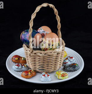 Easter eggs with beautiful ornaments placed in wicker basked on white plate with foil-wrapped chocolates - Stock Photo
