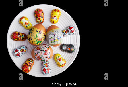 Easter eggs with beautiful ornaments and themed foil-wrapped chocolates on white plate - Stock Photo