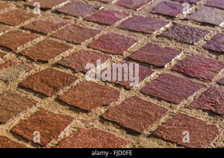 Decorative square tiled ground, wet after rain, shallow depth of field - Stock Photo
