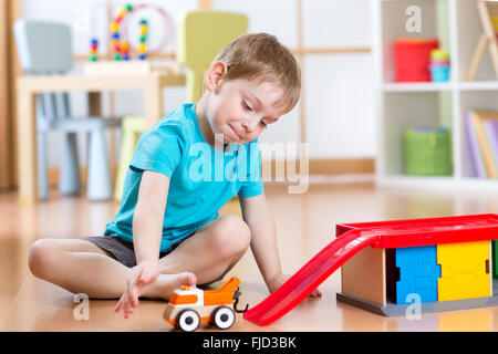 Little child playing with a toy car in nursery - Stock Photo